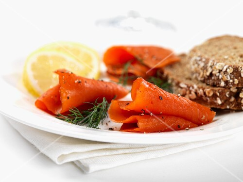 Sliced smoked salmon with lemon, dill and wholemeal bread