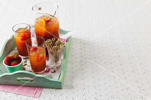 Pimms with strawberries and oranges on a tray