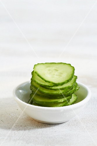 A stack of sliced cucumber in a small dish