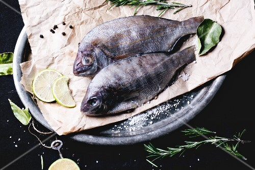Two seabream fish with rosemary, lime and sea salt server on baking paper