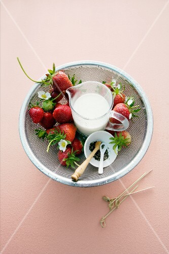 Fresh strawberries and a jug of milk in a colander