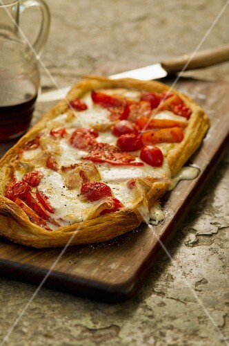 Tomato tart with cheese on a chopping board