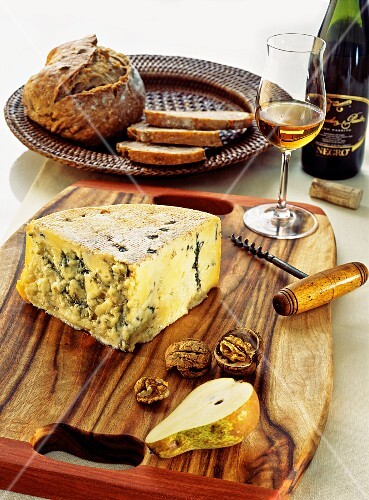 An arrangement of cheese with white wine, bread, nuts and pears