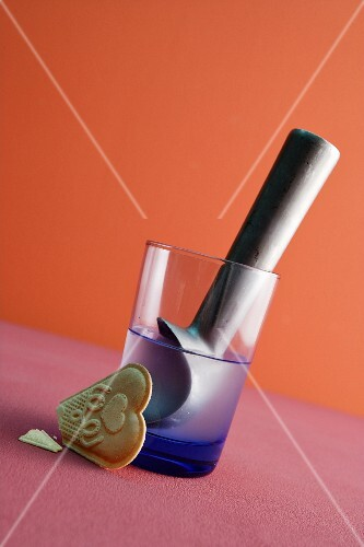 An ice cream scoop in a glass of water with a wafer