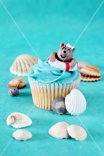 A coconut cupcake decorated with a swimming teddy bear surrounded by seashells