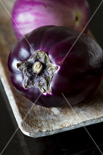Two aubergines in a wooden dish