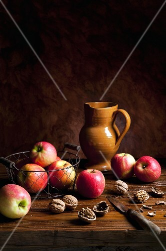 An arrangement featuring apples, walnuts, an earthenware jug and a knife