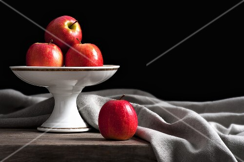 Apples on a cake stand with an elegantly draped cloth