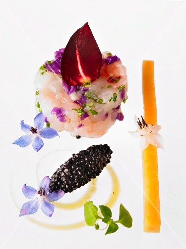 Crayfish tartar decorated with a rose petal, decorative long pepper and chervil flowers