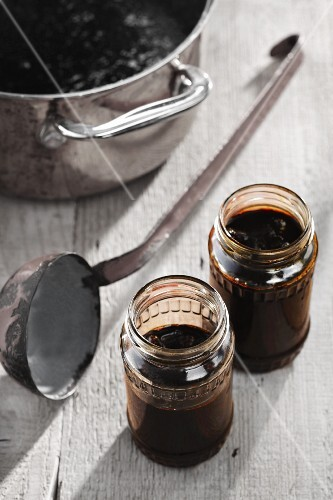 Powidl (stewed plums) in a saucepan and in jars