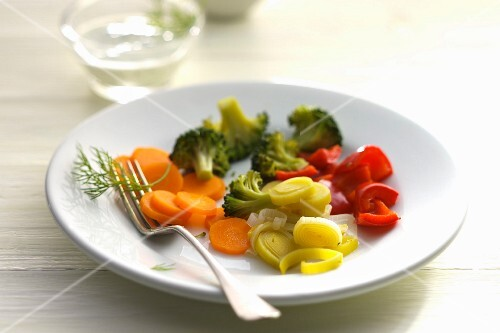 A plate of vegetables with carrots, leek, broccoli and peppers