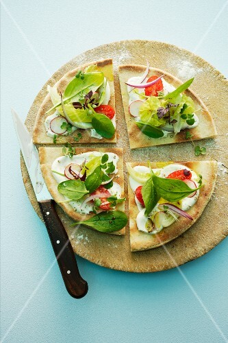A salad pizza topped with radishes, cherry tomatoes and spinach