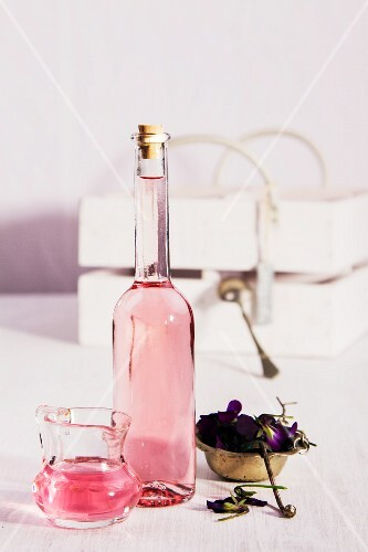 Violet vinegar in a bottle and a small glass jug