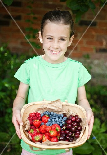 A girl with a basket of summer fruits