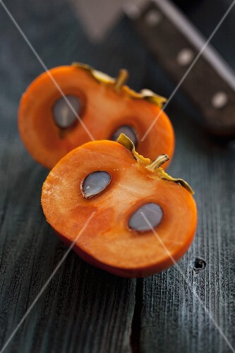 A sliced persimmon with seeds