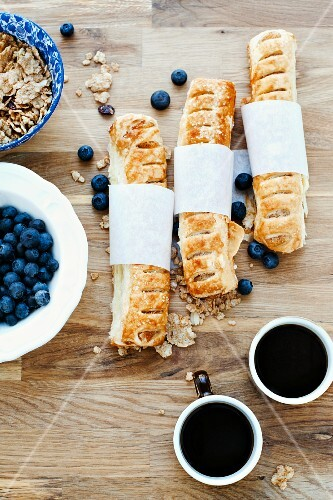 Baked pastries, blueberries, muesli and black coffee