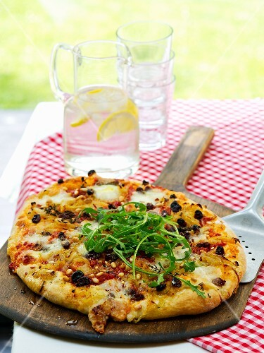 A pizza with rocket, raisins and pine nuts