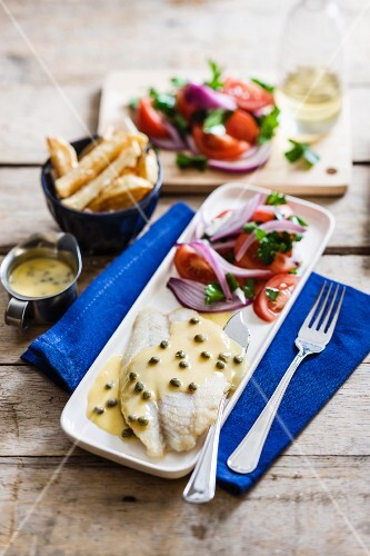 Fish fillet in a lemon and caper sauce with tomato salad and chips