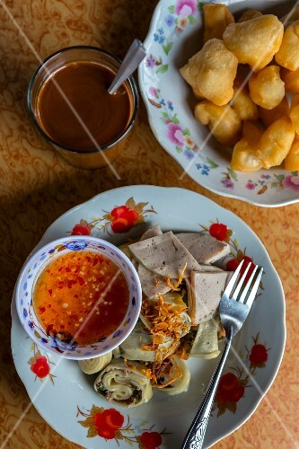 A Thai breakfast with coffee, fried pastries, Vietnamese sausage and rice flour rolls