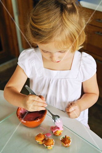 A little girl decorating mini muffins in a kitchen