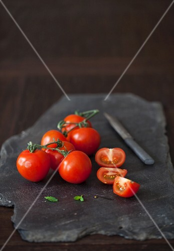 Tomatoes, whole and halved, on a black stone