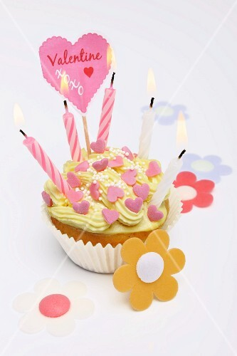 A cupcake decorated with sugar hearts and candles for Valentine's Day