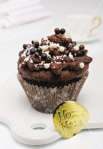 A chocolate cupcake decorated with chocolate and sugar pearls