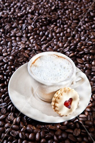 A cappuccino on coffee beans with a jam sandwich biscuit
