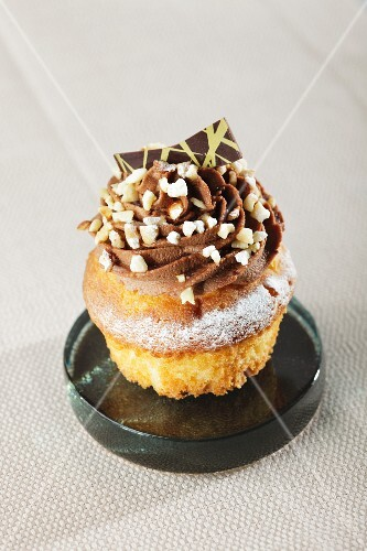 A cucpcake decorated with chocolate cream, nuts and chocolate sprinkles