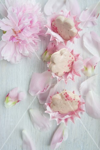Flower-shaped biscuits with rose icing scattered with peony petals