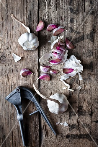 Garlic scattered on a rustic wooden surface with an old garlic press