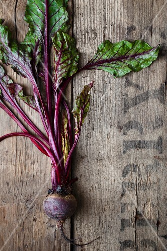 A beetroot with leaves on a rustic wooden surface