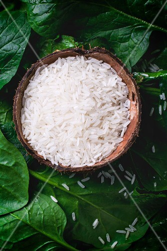 Jasmine rice in a coconut shell on a bed of spinach leaves