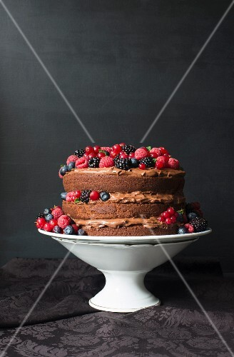 A layered cream chocolate cake decorated with fresh berries