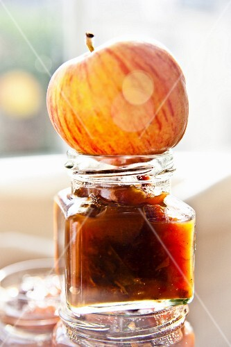 A jar of apple chutney with an apple on top in autumnal sunlight