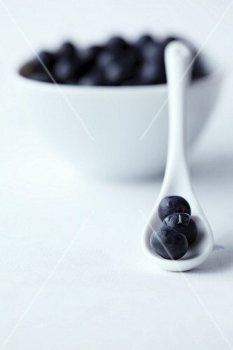 Blueberries on a white porcelain spoon and in a white bowl