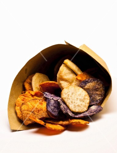 Various different coloured potato crisps in a paper bag
