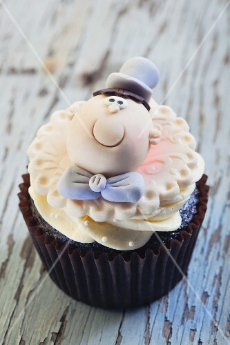 A wedding cupcake decorated with a groom