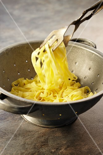 Linguine in a colander with pasta tongs
