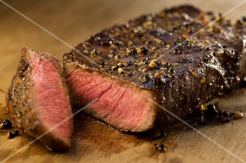 Beef steak, sliced, on a wooden chopping board