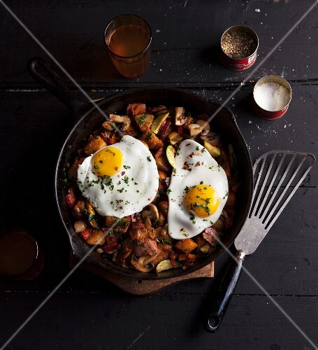 Fried potatoes with fried eggs in a pan