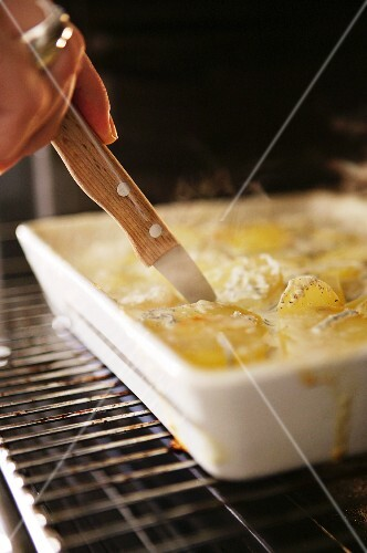 Potato gratin being cut from the baking dish