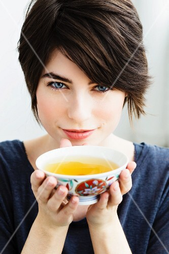 A woman holding a bowl of tea