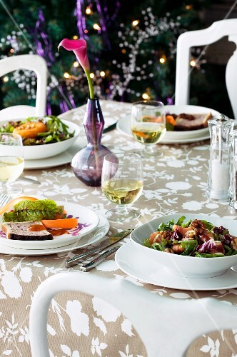 Appetisers, salads and white wine on a garden table
