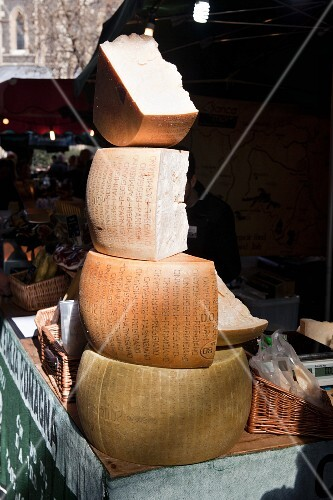 A stack of Parmesan cheese on a market stall