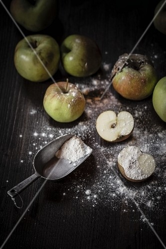 A halved apple and a flour scoop with flour sprinkled over the work surface and other apples in the background