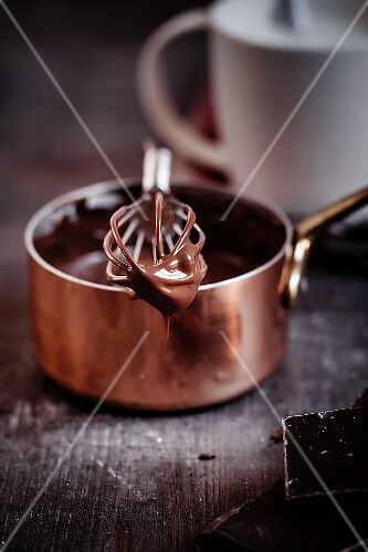 Melted chocolate dripped from a whisk balanced across a copper pot
