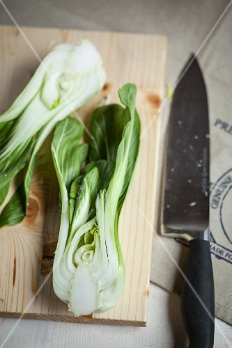 A hlaved bok choy on a wooden board with a knife