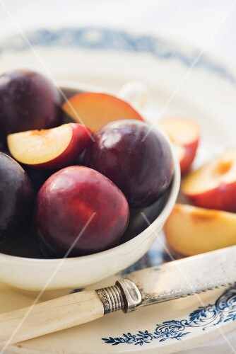 A bowl of plums with a vintage knife