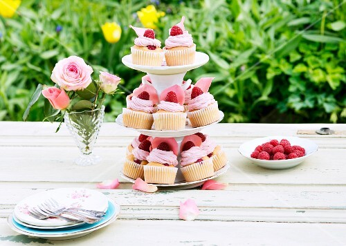 Raspberry cupcakes with rose petals on a cake stand on a garden table